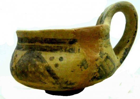 Handmade dipper cup in refined clay, restored, decorated with a matt-painted frieze of crosshatched triangles. From the excavations Stoop 1963-69 on the Acropolis of the Timpone della Motta. Height 7.9cm, diameter at rim 8.3cm. Middle Geometric period. Archaeological Museum of the Sibaritide, No. 64700.